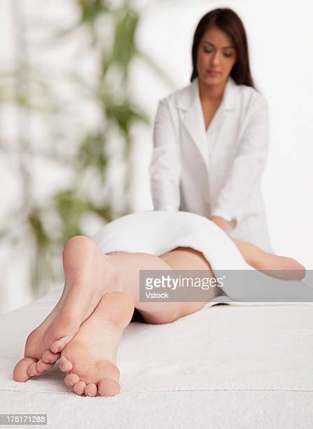 woman receiving massage - woman lying on stomach with feet up stock photos and pictures