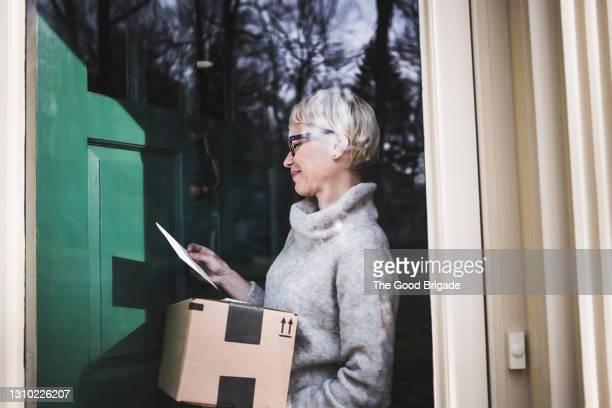 woman receiving package at front door of home - ontvangen stockfoto's en -beelden