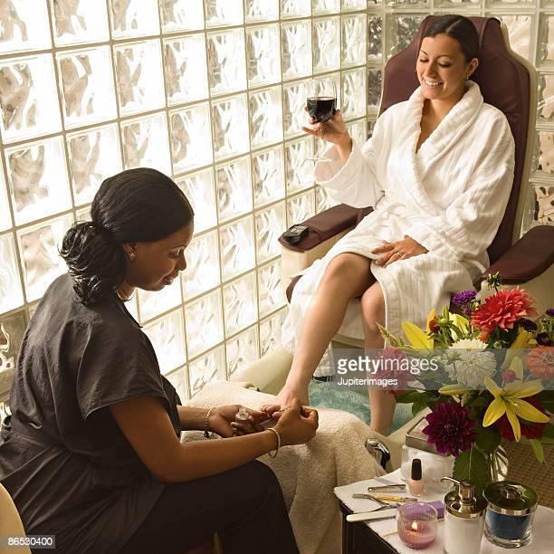 woman receiving pedicure - black pedicure stock-fotos und bilder
