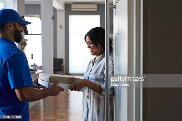 Woman receiving pizza from delivery person