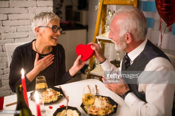 woman receiving present from husband - heart month stock photos and pictures