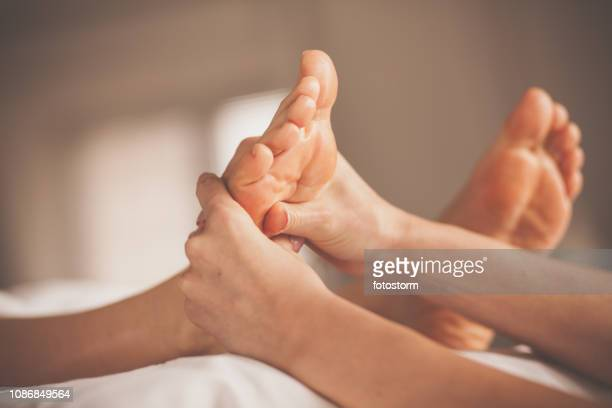 woman receiving reflexology treatment at spa - foot massage stock pictures, royalty-free photos & images