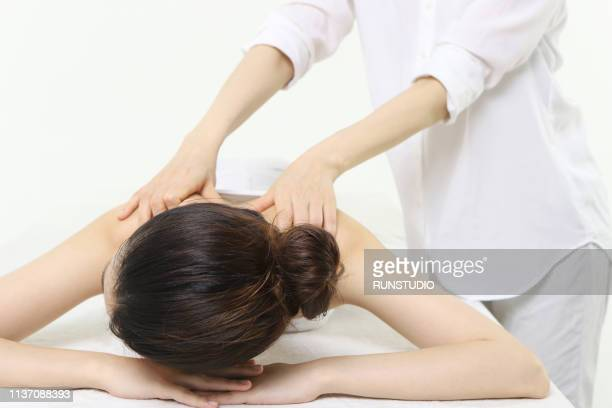 woman receiving shoulder massage - body massage japan stock pictures, royalty-free photos & images