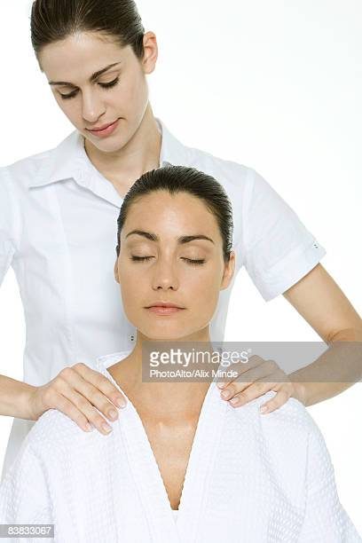 Woman receiving shoulder massage, relaxing with eyes closed