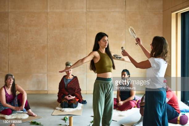 woman receiving smudge stick in smoke cleansing ritual - participant stock pictures, royalty-free photos & images