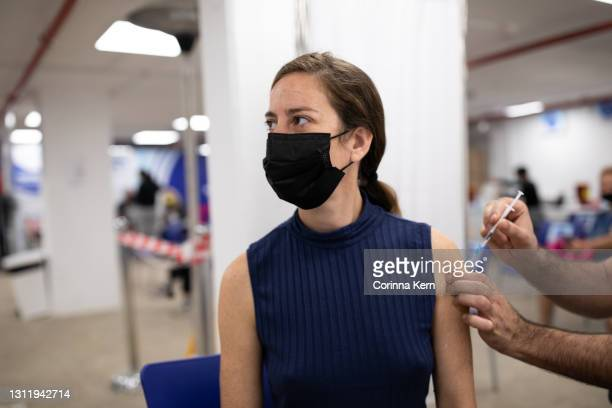 woman receiving vaccine - vaccination center stock pictures, royalty-free photos & images
