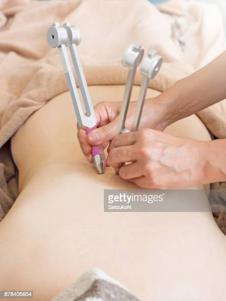 Woman recieving tuning fork therapy