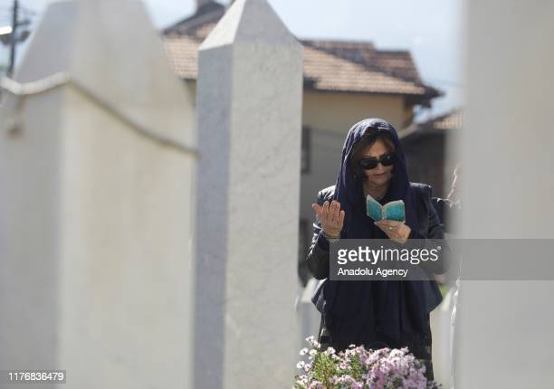 A woman recites holy Quran in front of the Bosnia and Herzegovina's first President Alija Izetbegovic's tomb during a ceremony marking the 16th death...