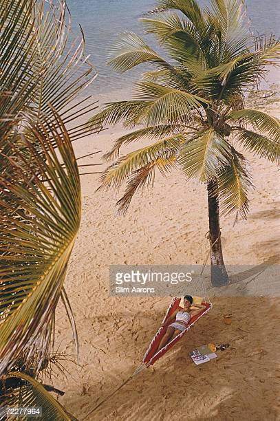 A woman reclining in a hammock hung between palm trees on the beach at the Caribe Hilton in San Juan Puerto Rico March 1956