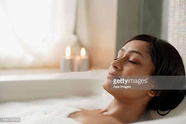 woman reclining in bathtub - escapism stock photos and pictures