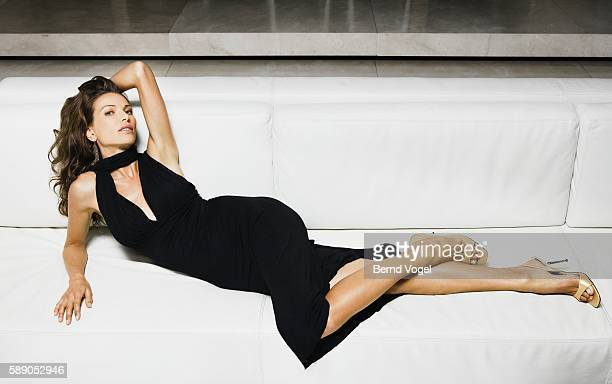 woman reclining on couch - beautiful long legs stock pictures, royalty-free photos & images