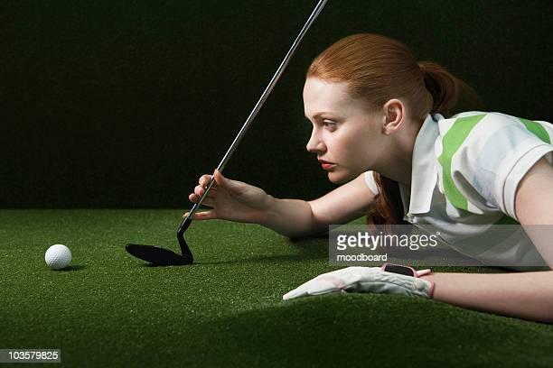 Femme couché sur le sol, en tenant golf club, à la recherche de golf de bal