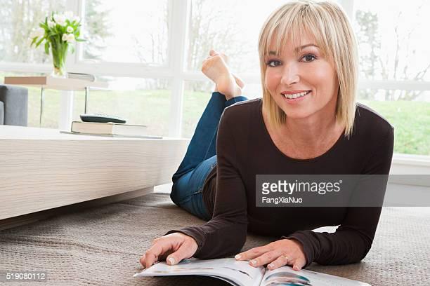 Woman reclining on floor reading magazine