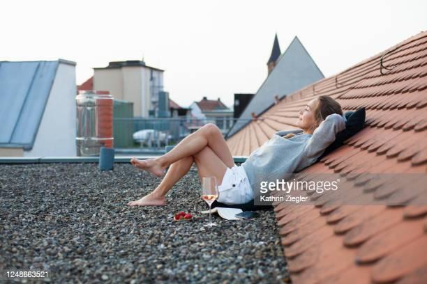 woman reclining on rooftop, enjoying a quiet moment - korte broek stockfoto's en -beelden