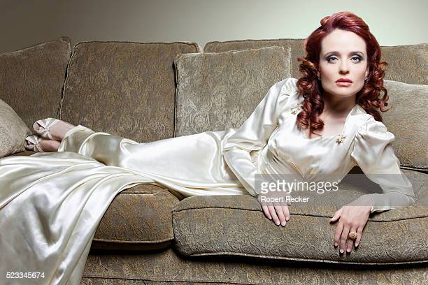 woman reclining on sofa - evening gown stock pictures, royalty-free photos & images