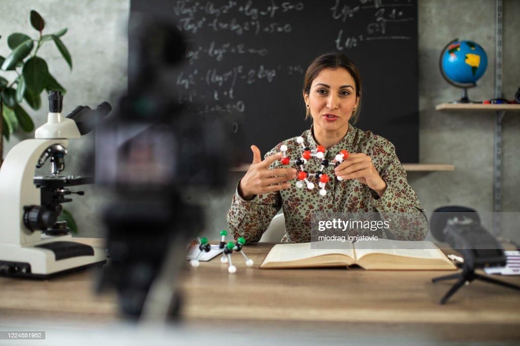 Woman recording chemistry lesson during coronavirus pandemic : Stock Photo