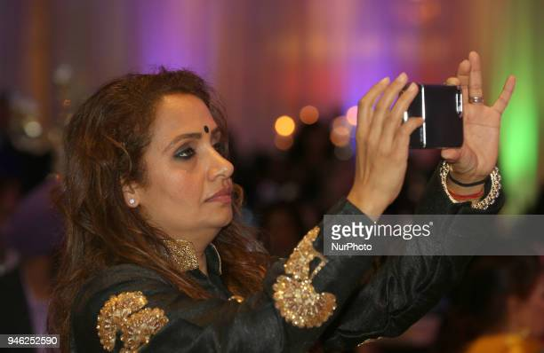 Woman records a video on her mobile phone as Bhangra superstar Malkit Singh performs during the William Osler Health Foundation's Holi Gala Event...