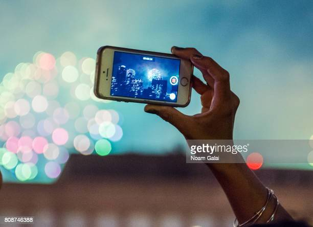 A woman records a video with her smartphone during New York City's 41st annual Macy's 4th of July fireworks on July 4 2017 in New York City