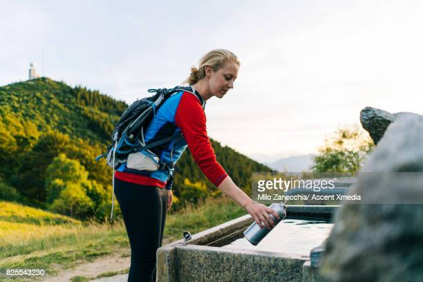 Woman refills water bottle from mountain fountain