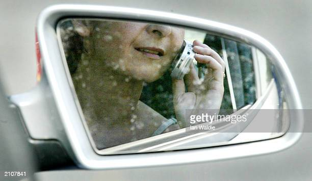 A woman reflected in a rearview mirror talks on a mobile phone while driving in traffic June 24 2003 in London England The government has announced...