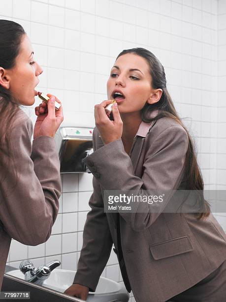 woman reflected in office washroom mirror applying make-up - vanity stock pictures, royalty-free photos & images