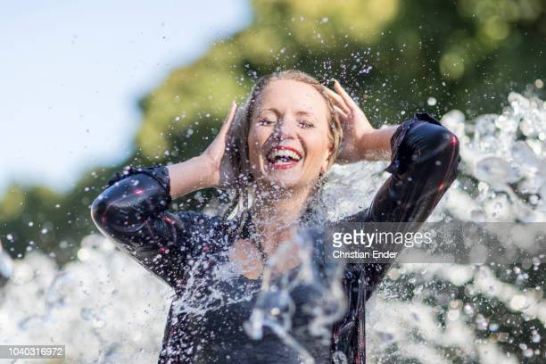 woman refreshes under fountains - hot high school girls stock photos and pictures