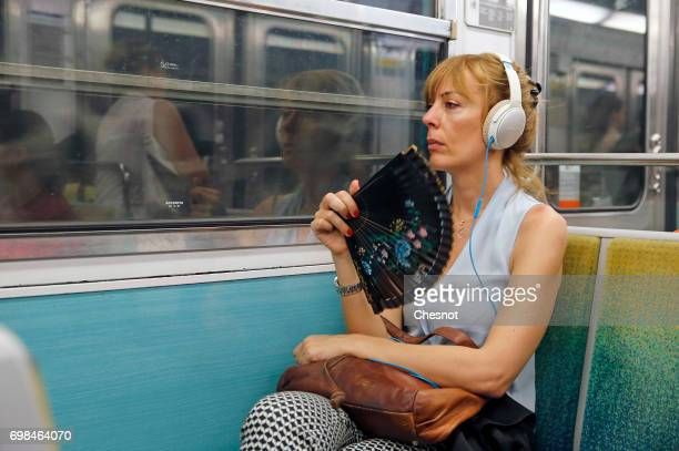 A woman refreshes with a fan of silk in the subway during the heat wave on June 20 2017 in Paris France France is currently experiencing a heat wave...