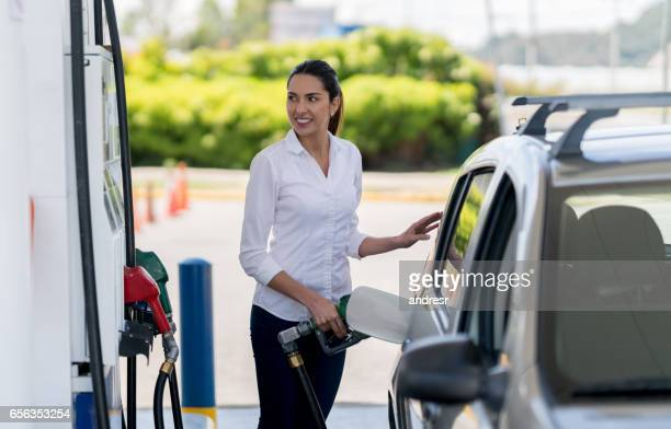 Woman refueling her car at a gas station