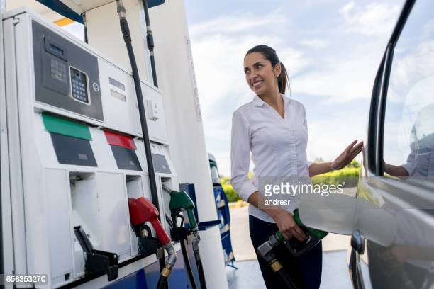 Woman refueling her car at a petrol station