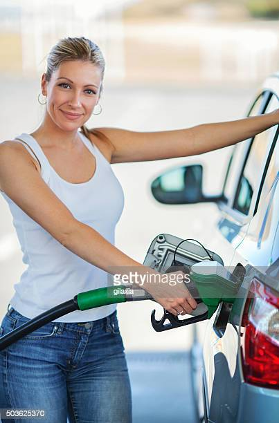 woman refueling her car at gas station. - gas tank stock photos and pictures