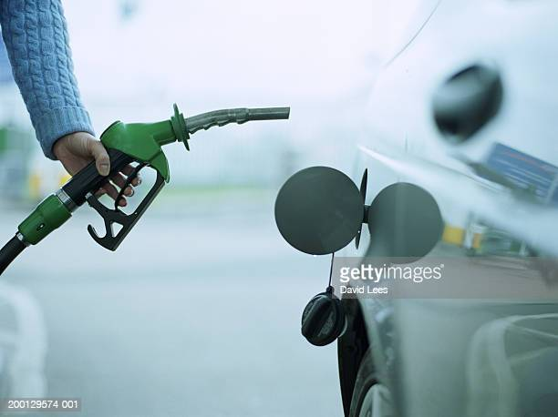 woman refuelling car at petrol station, close-up - gas station stock pictures, royalty-free photos & images