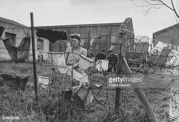 A woman refugee hangs her washing on a barbed wire fence at the building that was once a large film studio built by Mussolini After the Liberation of...