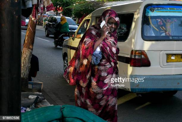 A woman refugees walking through the roadside refugee camp in front of the overcapacity immigration detention house in Jakarta Indonesia on June 19...