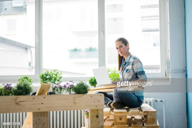 Woman refurbishing her new home with pallets, using laptop