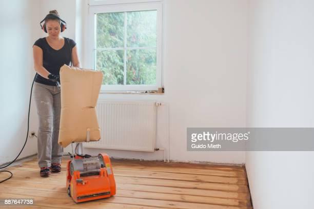Woman refurbishing old wooden floor.