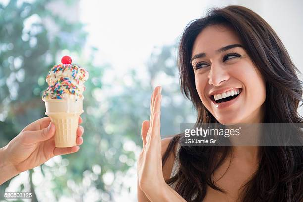 woman refusing ice cream cone - weigeren stockfoto's en -beelden
