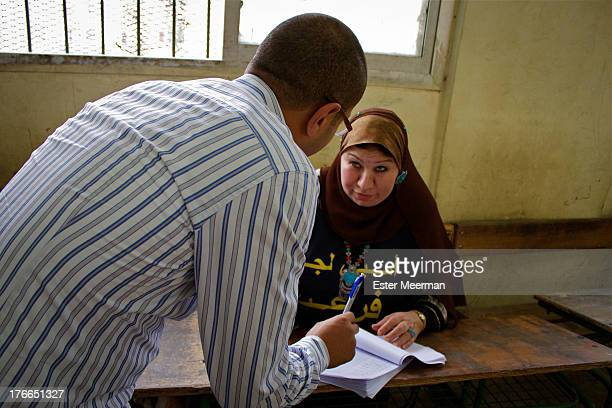 CONTENT] A woman registers a man that wants to cast his vote in the first round of the Egyptian presidential elections on the 23rd of May 2012
