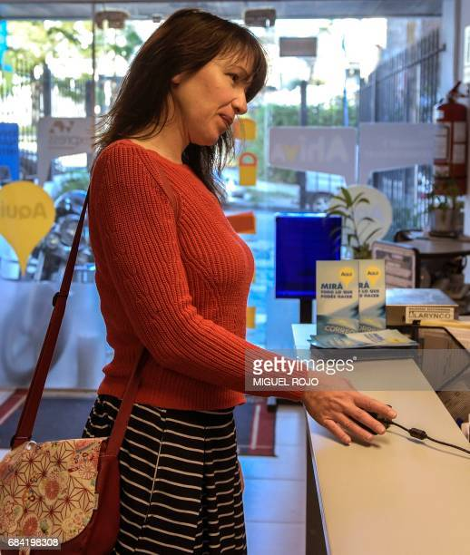 A woman registers as a marijuana buyer at a state post office in Montevideo on May 2 2017 Uruguay which in July will become the first country selling...