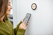 Woman regulating heating temperature with phone and thermostat at home