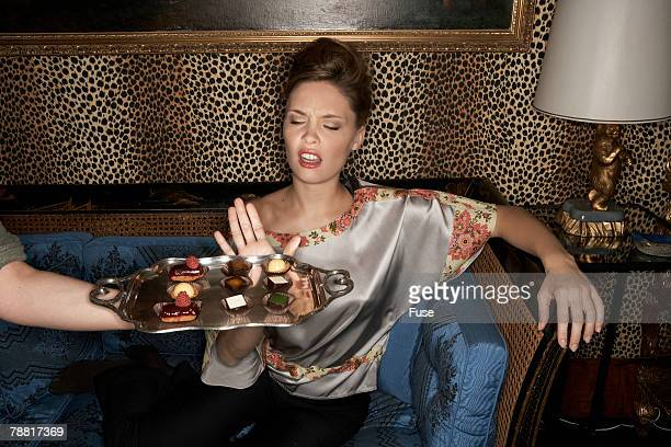 Woman Rejecting a Tray of Chocolates