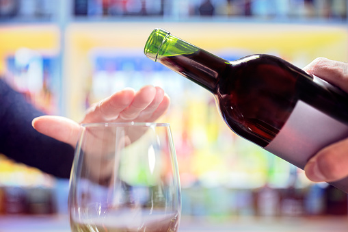 Woman rejecting more alcohol from wine bottle in bar 1042617766