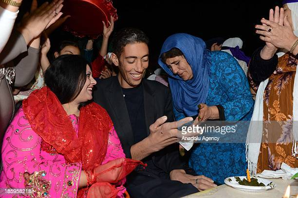 A woman relative applies henna on the hands of the World's tallest man Sultan Kosen and his fiancee Merve Dibo during their henna night the ceremony...