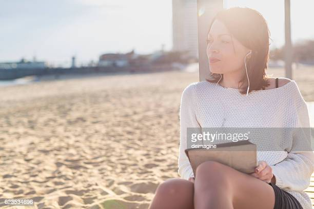 Woman Relax and Using a Tablet at the Beach
