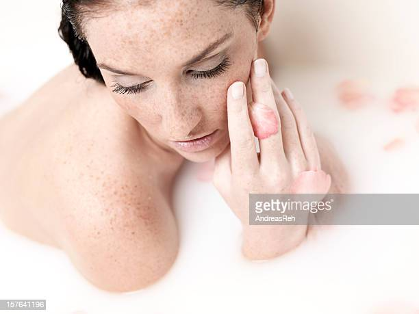 Woman relax in milk bath with petals,