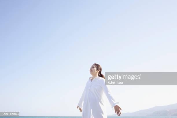 女性が海辺でリラックス - 期待 ストックフォトと画像