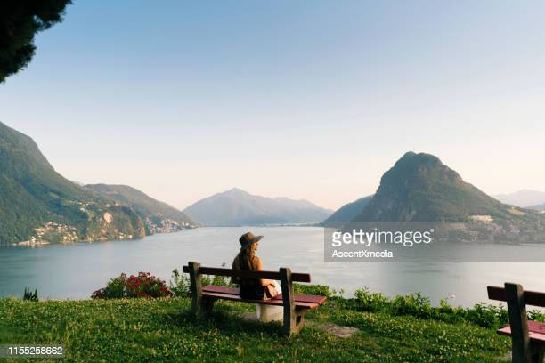woman relaxes above lake and mountains on bench - tranquil scene stock pictures, royalty-free photos & images