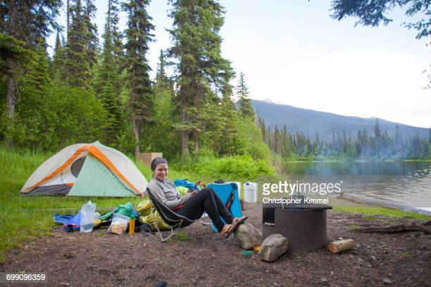 a woman relaxes at a lakeside campsite in bowron lake provincial park - cadeira dobrável - fotografias e filmes do acervo
