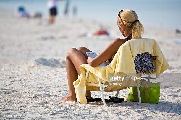 Woman Relaxes at Beach Doing Puzzle
