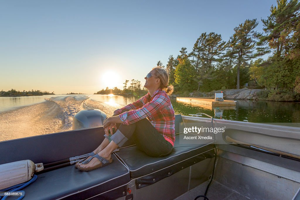 Woman relaxes at rear of motorboat, on lake : Stock Photo