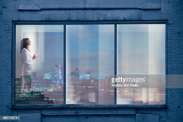 Woman relaxes at the window of her city apartment